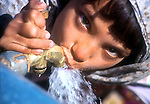 In the Shamshatoo camp, an Afghan refugee girl enjoys drinking clean water..
