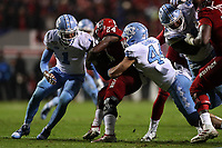 RALEIGH, NC - NOVEMBER 30: Zonovan Bam Knight #24 of North Carolina State University is tackled by Jeremiah Gemmel #44 and Myles Dorn #1 of the University of North Carolina during a game between North Carolina and North Carolina State at Carter-Finley Stadium on November 30, 2019 in Raleigh, North Carolina.