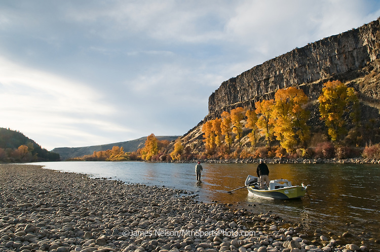 An angler in a drift boat watches his fishing partner fly fish for trout during an autumn evening on the South Fork of the Snake River, Idaho.