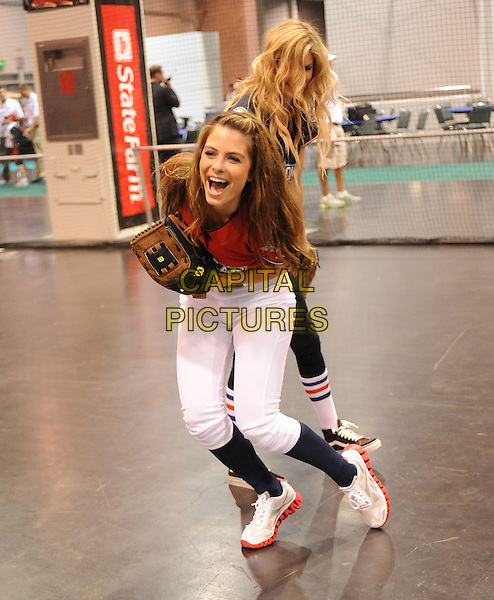 MARISA MILLER & MARIA MENOUNOS .At the MLB All Star Fanfest Batting Practice held at The Anaheim Convention Center , the precursor to The All Star Legends Celebrity Softball game in Anaheim, California, USA..July 11th, 2010.full length red black top baseball mitt glove socks white trousers leggings smiling bending laughing .CAP/RKE/DVS.©DVS/RockinExposures/Capital Pictures.