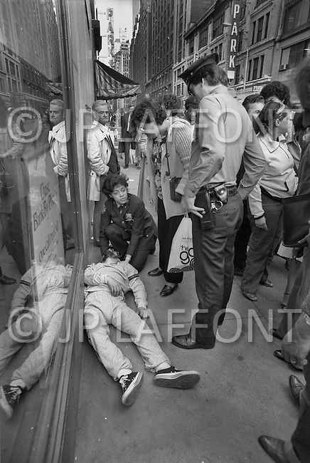 May, 1980. Manhattan, New York City, NY. Bystanders gather around two NYPD officers assisting a man suffering a drug overdose on a Times Square corner. It happens so often it does not stop the traffic.<br />