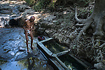 "November 09, 2014. ""Water it´s the real thing""<br /> Felipe Ruiz, 65 years old, washes himself in a place called El Caballo with contaminated water. He doesn' t have water at home and he has to walk near two hours to El Caballo. The people of Nejapa in El Salvador, have no drinking water because the Coca -Cola company overexploited the aquifer in the area, the most important source of water in this Central American country. This means that the population has to walk for hours to get water from wells and rivers. The problem is that these rivers and wells are contaminated by discharges that makes Coca- Cola and other factories that are installed in the area. The problem can increase: Coca Cola company has expansion plans, something that communities and NGOs want to stop. To make a liter of Coca Cola are needed 2,4 liters of water. ©Calamar2/ Pedro ARMESTRE"