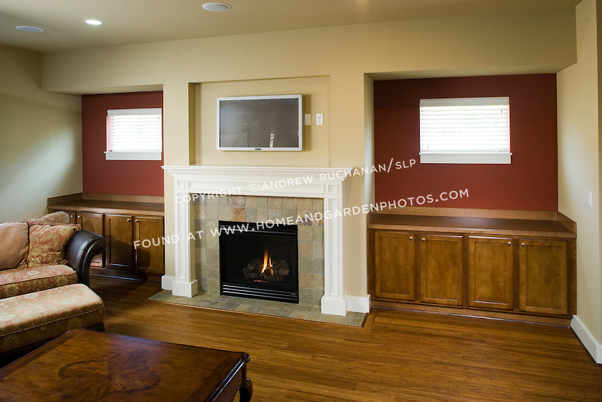 A builder spec home in the Pacific Northwest suburbs of Seattle offers a sitting / tv room with wood floors, a gas fireplace, a tile hearth and fireplace surround, and dark stained built-in cabinets for storage and display.