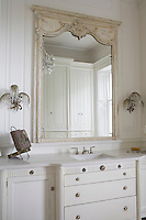 A carved mirror hangs above a washbasin set in a built-in cupboard and drawer unit in a neutral bathroom.