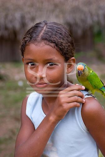 Pará State, Brazil. Aldeia Paquissamba (Juruna). Mayara Juruna with pet parrot.