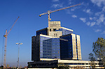 Sofia, Bulgaria. Modern concrete and glass building under construction with a crane.