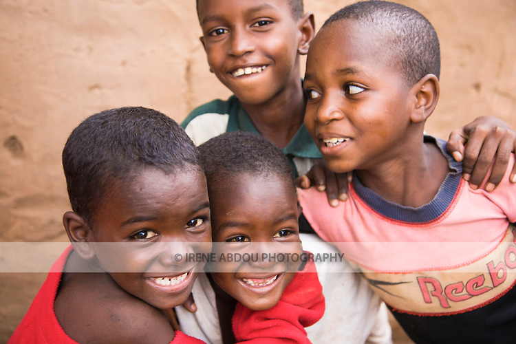 Three children from the traditionally pastoralist Fulani ethnic group playfully pose for the camera in Ouagadougou, Burkina Faso.