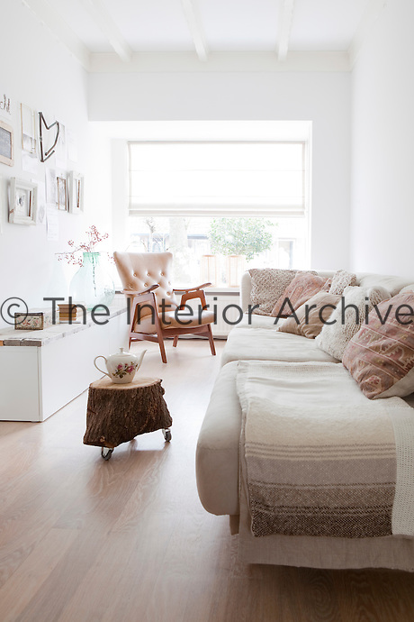 The living room tapers towards the front window and is furnished with a comfortable sofa filled with scatter cushions