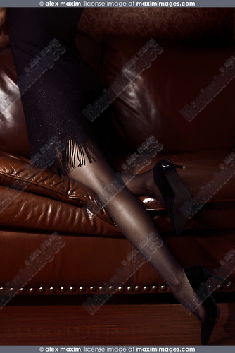 Legs in black stockings, sexy woman in black dress and high heel shoes leaning on a brown leather couch in a dimly lit room