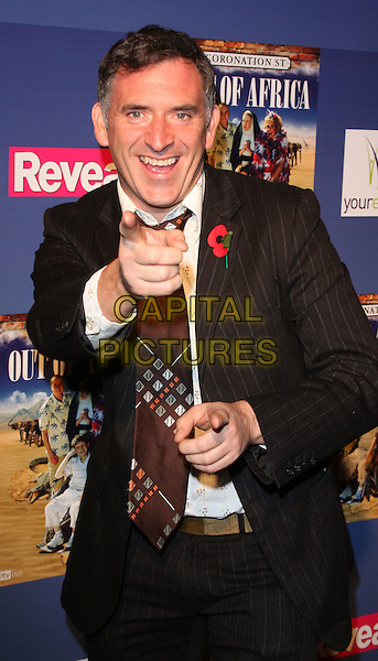 """TONY AUDENSHAW.Coronation Street """"Out Of Africa"""" DVD Premiere at Odeon Cinema, The Printworks, Manchester, England..November 4th, 2008.half length black suit jacket brown wide tie poppy hands pointing .CAP/ROS.©Steve Ross/Capital Pictures."""