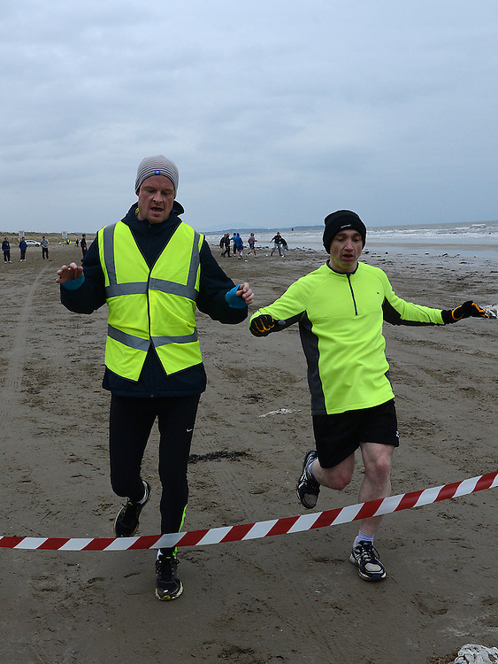 Val Cobball and Peter Sheridan cross the line together to win the St Mary's Drumcar 5K run on Bettystown beach. Photo:Colin Bell/pressphotos.ie
