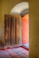 Entry door with tile floor, stunning light, and adobe wallsl at Mission La Purisima State Historic Park, Lompoc, California.  Mission La Purisima, founded in 1787 by Franciscan Padre Presidente Fermin Francisco Lasuen. La Purisima was the eleventh mission of the twenty-one Spanish Missions established in what later became the state of California.