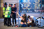 © Joel Goodman - 07973 332324 . 11/09/2016 . Manchester , UK . A woman reaches out her hand towards a police officer as another is tended to on the ground , on Withy Grove . Revellers out in Manchester City Centre . Photo credit : Joel Goodman
