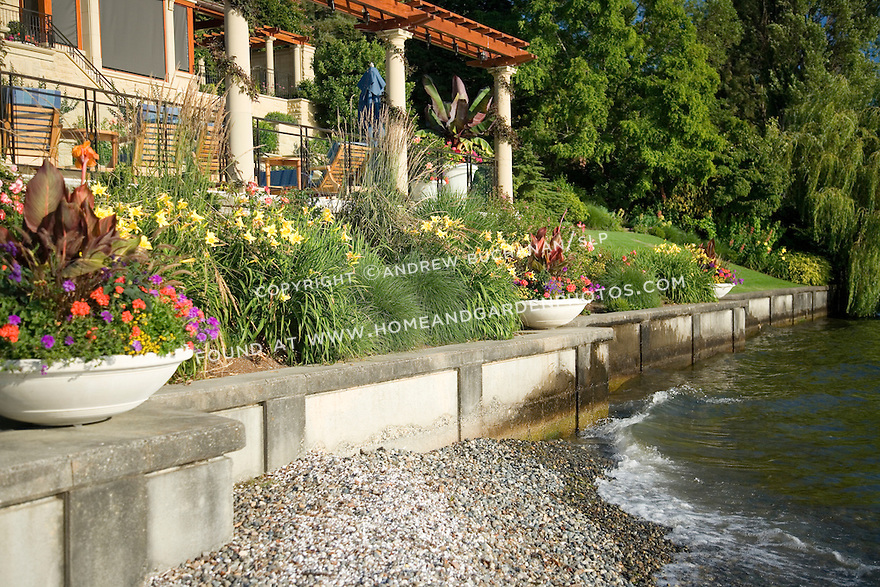 garden pots made by Longshadow are filled with lush tropical plants and colorful annuals on this sunny, waterfront bulkhead wall