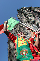 A Portugal Fan cheers and dances along with other Portugese fans carrying and beating drums while walking past the Kölner Dom cathedral  in Cologne, Germany.  The fans were getting ready for the Portugal national soccer team's first round FIFA World Cup match against Angola in Cologne, Germany on Sunday, June 11th 2006.