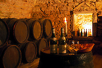 Chateau Pierreclos Winery, cellar with barrels, bottles, glasses, candles and bread for tasting. Maconnais Region, France
