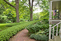 Problem site: Shade of big trees. Solutions include foliage shady plant groundcovers Pachysandra terminalis, hostas, Polygonatum Solomon's Seal, next to house, porch, steps, lawn, brick walkway, American flag patriotic. Big trees casting shade