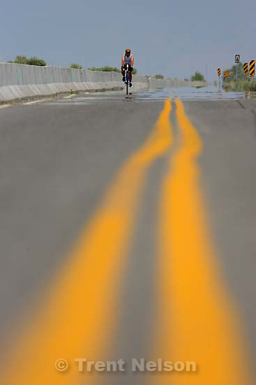 Jerry Geurts of Bountiful braves 95 degree weather covering miles on his bicycle while training for a triathlon. Riding west of Salt Lake City on a frontage road along I-80, Geurts's advice on keeping cool: &quot;Keep moving.&quot;. 7.12.2006<br />