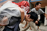 Newlyweds Ren Jing (bride) and Da Fen race to their new apartment as friends try to hold them back in Pingliang, Gansu, China.  The couple are members of the Hui ethnic minority, a Muslim ethnic minority native to northwestern China.