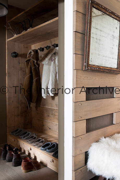 A wooden garderobe in the entrance with a row of slippers ready for guests