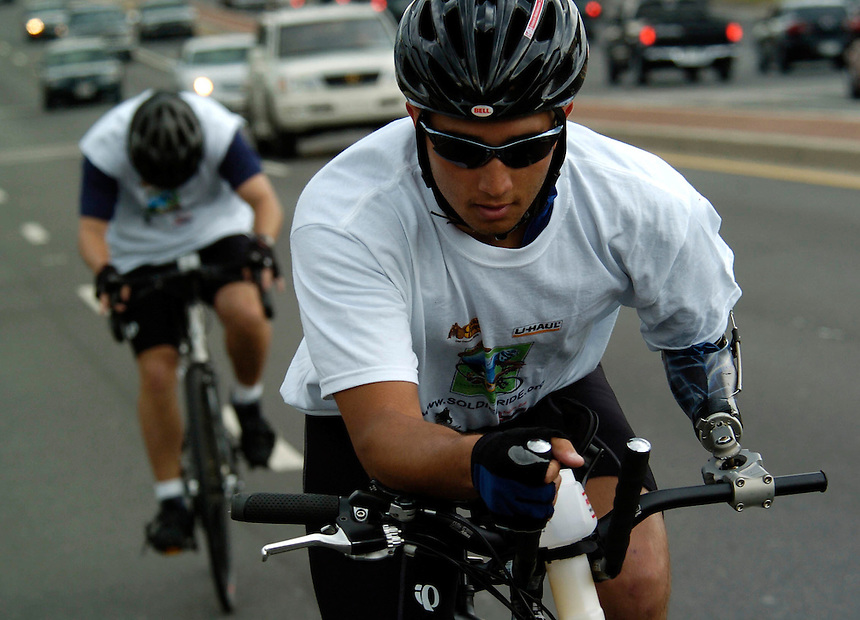 """Domingo Soto, 23, rides from Annapolis to Washington, DC with his """"blue lightening"""" prosthetic clamped to the handle bar of his bike. Soldier Ride cyclist are riding across the country in hopes of raising public awareness and support for the needs of the severely injured servicemen and women injured in the current military conflicts around the world. May, 13, 2006 . (James J. Lee / Army Times Staff)."""