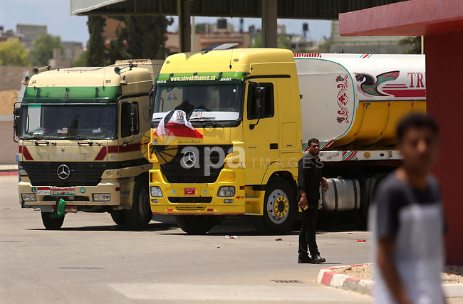 Palestinians walk as Egyptian trucks carrying fuel arrive to Gaza's power plant in Nusseirat, in the central Gaza Strip after entering the southern Gaza Strip from Egypt through the Rafah border crossing on June 21, 2017. Egypt began to deliver a million litres of fuel to Gaza, a Palestinian official said, in an attempt to ease the Palestinian enclave's desperate electricity crisis. The fuel, trucked in through the Rafah border between Egypt and Gaza, will be routed to the territory's only power station -- closed since April due to fuel shortages. Photo by Ashraf Amra