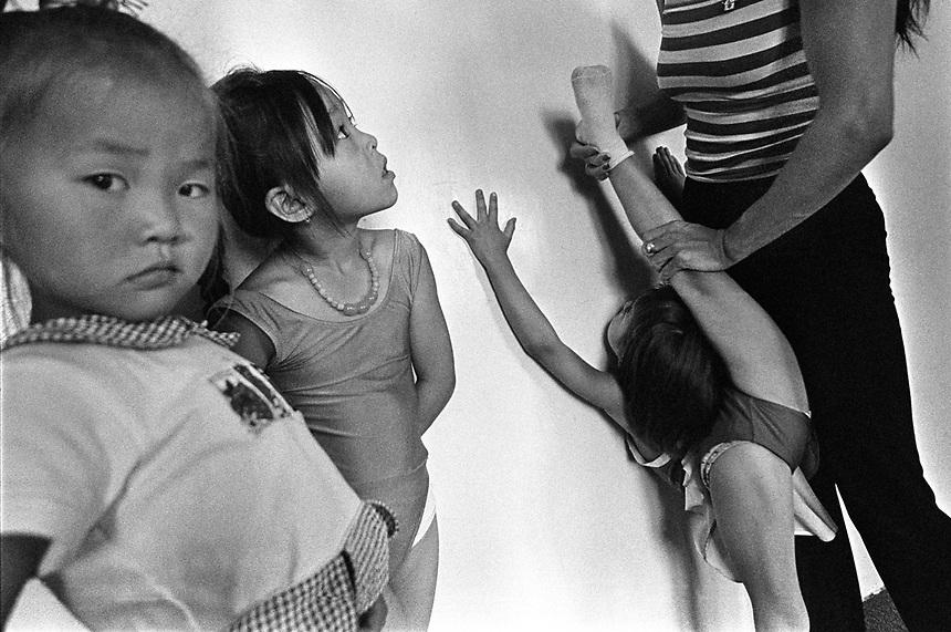 Mongolian children wait their turn to have a teacher help stretch their legs.