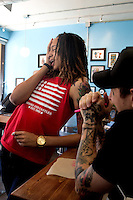 Jun. 10, 2013; Phoenix, AZ, USA: Phoenix Mercury center Brittney Griner reacts as she talks to tattoo artist Jason Anthony inside the Golden Rule Tattoo shop in downtown Phoenix. Mandatory Credit: Mark J. Rebilas-