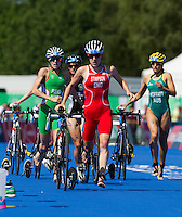 24 JUL 2014 - GLASGOW, GBR - Jodie Stimpson (ENG) (centre, in red and white) from England leads the way through transition at the end of the bike during the elite women's 2014 Commonwealth Games triathlon in Strathclyde Country Park, in Glasgow, Scotland (PHOTO COPYRIGHT &copy; 2014 NIGEL FARROW, ALL RIGHTS RESERVED)<br /> *******************************<br /> COMMONWEALTH GAMES <br /> FEDERATION USAGE <br /> RULES APPLY<br /> *******************************