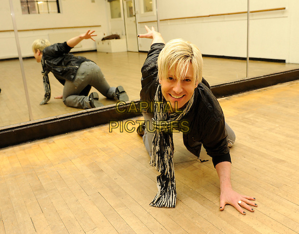 ANDREW STONE.The dancer from cult TV hit 'Pineapple Dance Studios' pictured at Pineapple Studios, London, England..March 10th, 2010.full length black leather jacket scarf white grey gray crouching kneeling on floor smiling jeans denim reflection mirror .CAP/FIN.©Steve Finn/Capital Pictures.