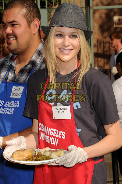 STEPHANIE PRATT .LA Mission & Anne Douglas Center's Thanksgiving Meal For The Homeless held at the Los Angeles Mission, Los Angeles, California, USA, .25 November 2009..Celebs celebrities doing charity work .half length t-shirt hat fedora trilby smiling black grey gray tweed wool pattern red apron plate of food gloves .CAP/ADM/BP.©Byron Purvis/Admedia/Capital Pictures