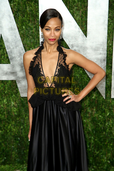 Zoe Saldana.2013 Vanity Fair Oscar Party following the 85th Academy Awards held at the Sunset Tower Hotel, West Hollywood, California, USA..February 24th, 2013.oscars half length black dress peplum lace plunging neckline cleavage silk satin skirt hand on hip red lipstick .CAP/ADM/SLP/DOW.©Dowling/StarlitePics/AdMedia/Capital Pictures