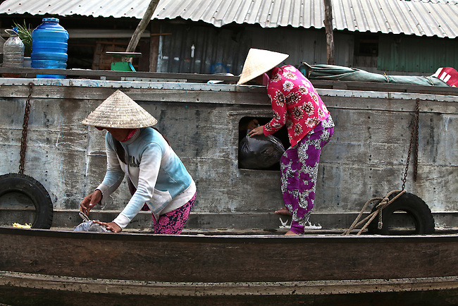 Two women make a pickup from a boat on the Hau River in the Mekong Delta, south of Can Tho, Vietnam. Sept. 30, 2011.