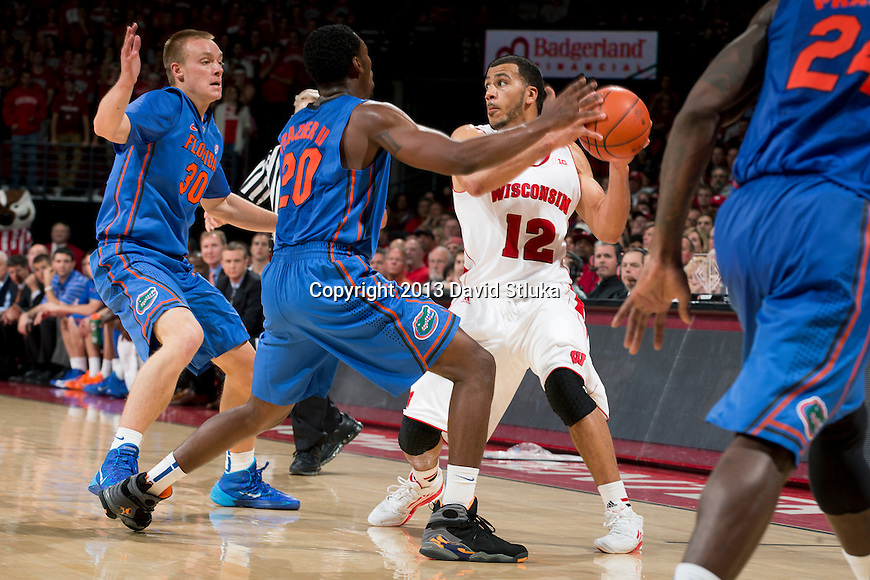 Wisconsin Badgers guard Traevon Jackson (12) handles the ball against Florida Gators Michael Frazier II (20) and Jacob Kurtz (3) during an NCAA college basketball game Tuesday, November 12, 2013, in Madison, Wis. The Badgers won 59-53. (Photo by David Stluka)