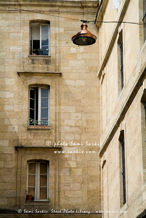Lantern hanging from a wire with apartment buildings in the background, Bordeaux, France.