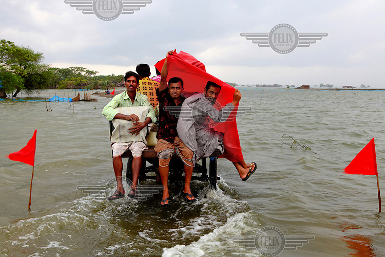 A group of men travel on the back of an auto rickshaw through flood waters that have innundated the Satkhira district. The submerged road has been marked by red flags. Each year limited flooding helps to enrich the soil and create very fertile farm land. In turn, this results in a high population density on the flood plain. However, the low lying land is also prone to extreme flooding events that are very destructive to both the economy and human life.