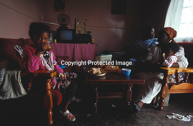 LSRURAL30097.People Rural Eastern Cape. Young girl drinking tea and eating dry bread from the table. Family, 2 women 1 with baby other looking out of the window. Lounge suite, small television. Low income family. Poverty. 12/2000..©Per-Anders Pettersson/iAfrika Photos