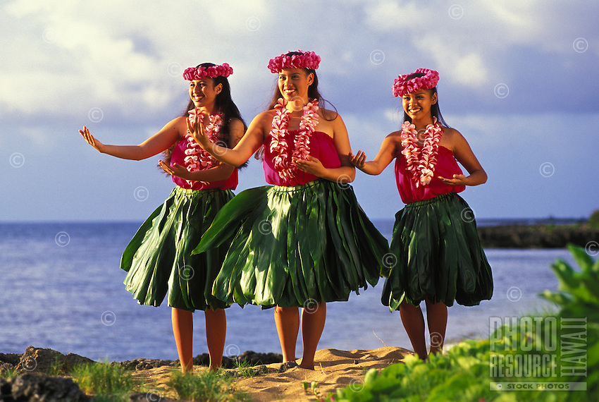 Three hula dancers with plumeria leis and ti leaf skirts near ocean