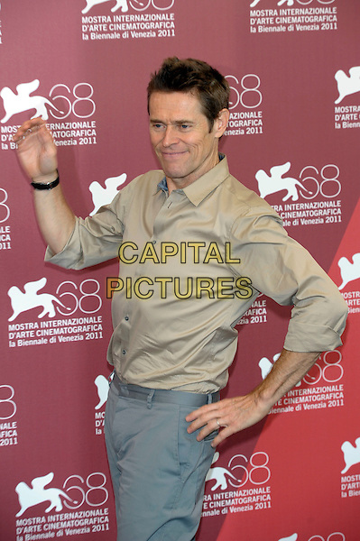 Willem Dafoe.'4:44 Last Day on Earth'  photocall 68th Venice Film Festival, Italy 5th September 2011.half length beige shirt grey gray trousers hand on hip posing funny.CAP/PL.©Phil Loftus/Capital Pictures.