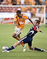 New England Revolution midfielder Steve Ralston (14) slide tackles Houston Dynamo midfielder Ricardo Clark (13).  New England Revolution defeated Houston Dynamo 2-0 at Robertson Stadium in Houston, TX on June 12, 2008.