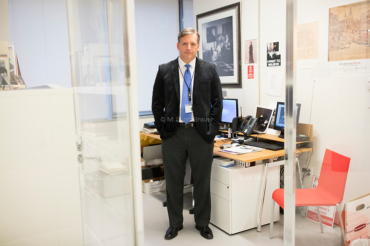 """Anthony Amore is the Directory of Security and Chief Investigator at the Isabella Stewart Gardner Museum in Boston, Mass., USA, seen here in his office on Tues., Dec. 5, 2017. Part of Amore's ongoing work is the investigation into the 1990 theft of 13 pieces from the museum: 10 paintings, 2 objects, and 1 etching. Among the paintings stolen were works by Rembrandt, Vermeer, Degas, and Manet. At right, hanging on the wall, is a reproduction of Vermeer's """"The Concert."""" The painting is one of those stolen in the heist."""