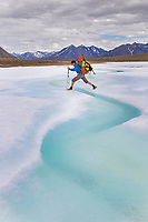Backpacker steps over water melting on the aufeis of the Ribdon River in the Arctic National Wildlife Refuge, Brooks Range, Arctic Alaska.