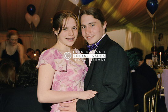 Teenage couple standing with arms around each other; wearing black tie and ball gown,