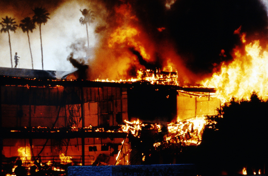 Mini-mall goes to waste in flames during the 1992 Rodney King riots as one person uses a garden hose on top of the adjacent building. photo by Jim Mendenhall/Los Angeles Times.