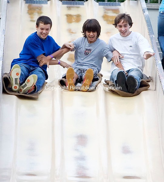 WOODBURY, CT- 29 AUGUST 2008- 082908JT03-<br /> From left, Neil Edwards, Justin Lewis, and Dan Perruci, all 13, try to slow each other down as they race on the &quot;Fun Slide&quot; to the bottom at the Woodbury Fire Department's annual carnival at Hollow Park on Friday.<br /> Josalee Thrift / Republican-American