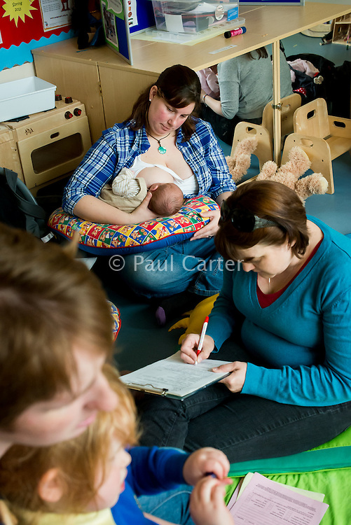 "A mother breastfeeding her baby at a drop-in breastfeeding support centre while the breastfeeding consultant takes some notes from another mother.<br /> <br /> Image from the ""We Do It In Public"" documentary photography project collection: <br />  www.breastfeedinginpublic.co.uk<br /> <br /> Dorset, England, UK<br /> 17/04/2013"