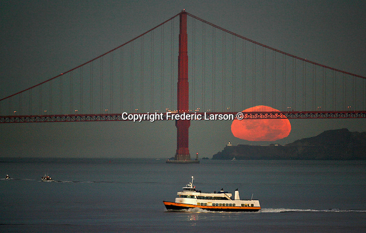 The full moon set behind the Golden Gate Bridge as seen from San Francisco Treasure Island, California.