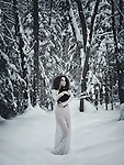 Beautiful woman in white long dress walking in the snow with a black cat in her hands in winter nature scenery