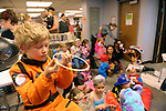 Hayden Brundage, 6, left, checks out his glow-in-the-dark headband as other children watch TV at the Carson City Library Monday, Oct. 27, 2014. As part of the library's Halloween festivities, dozens of children decorated pumpkins and took part in a costume contest.