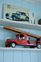 An old fire engine, a retro picture and a letter M for Marius are displayed on the shelves in his bedroom